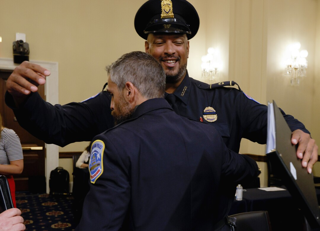 Officer Michael Fanone is embraced by officer Harry Dunn.