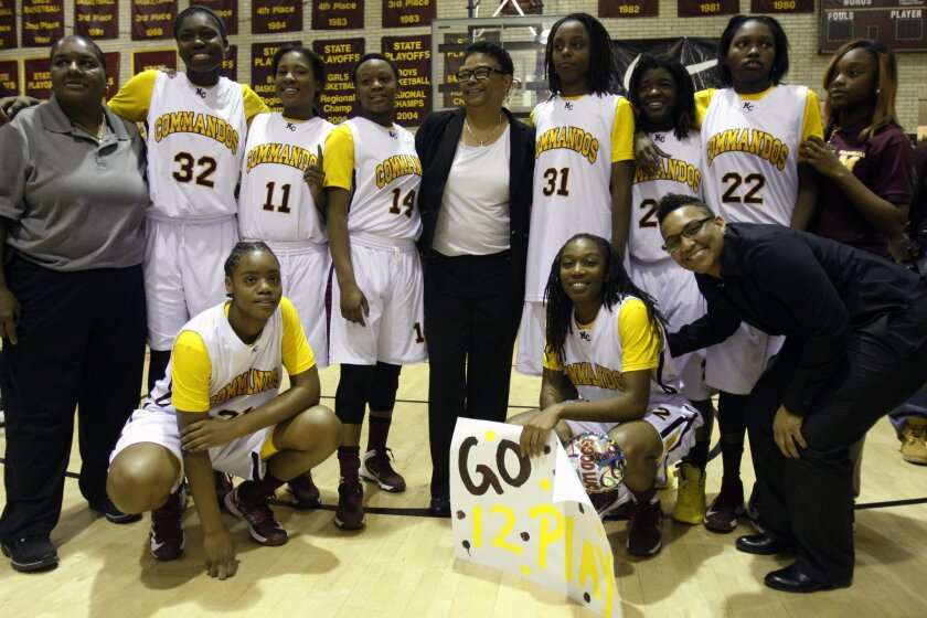 Dorothy Gaters, center, coach of the girls' basketball team at John Marshall Preparatory High School, poses for photos with her team and assistant coaches after her 1,000th career win on Tuesday, Nov. 18, 2014, in Chicago. Gaters has won more games than any high school basketball coach in Illinois,