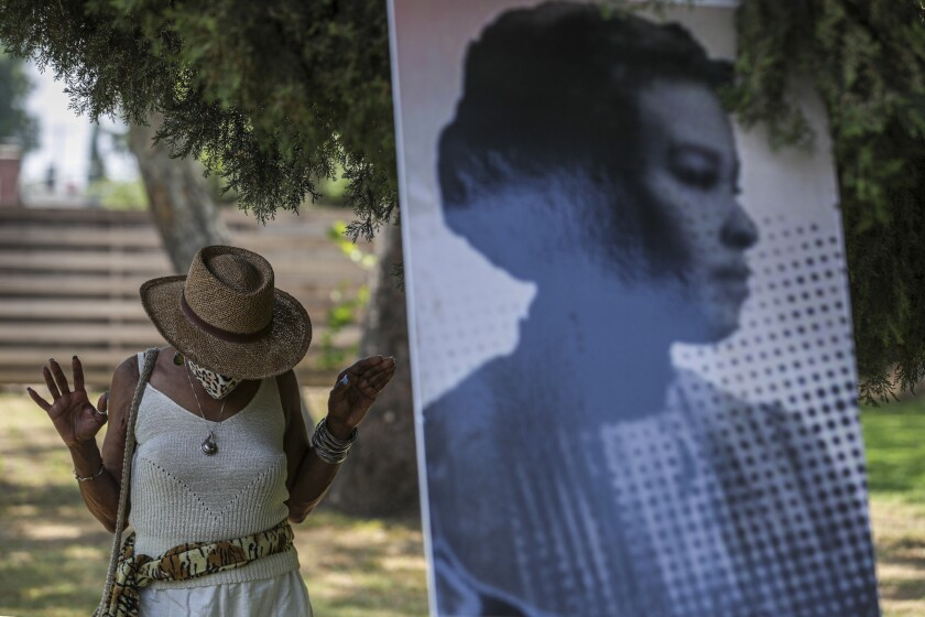 A woman stands outside near a blown-up vintage photograph of a woman