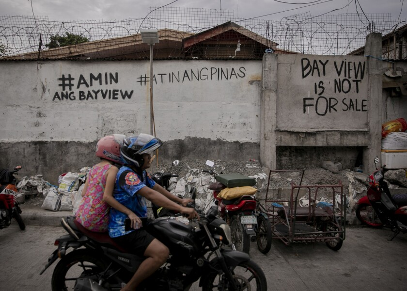 """""""Bayview is ours,"""" and """"The Philippines is ours"""" are written in Filipino on a wall along Bayview Dri"""