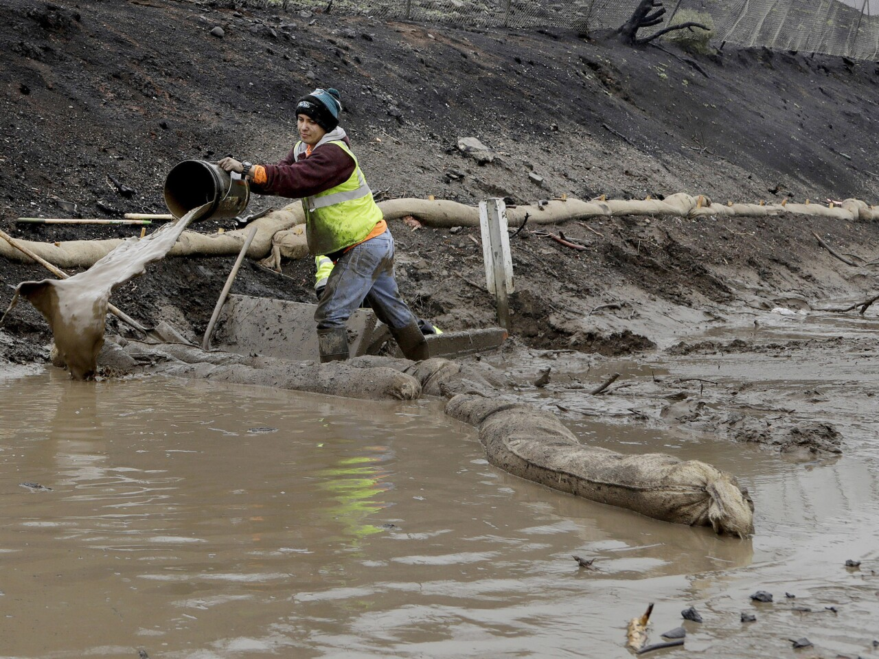A worker uses a bucket to clear out a drainage ditch along Pacific Coast Highway, north of El Matador Beach in Malibu.