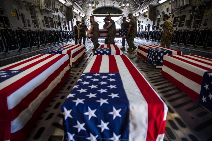 U.S. Marines carry a casket inside a U.S. Air Force C-17 Globemaster III at Marine Corps Air Station Miramar