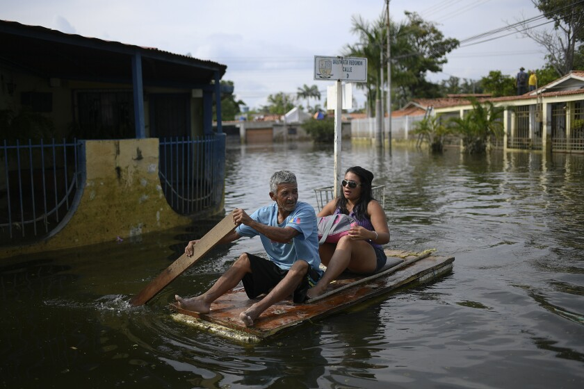 A man utilizes a door as a makeshift raft as he transports a woman through the inundated streets of the Mata Redonda neighborhood of Maracay, Venezuela, Wednesday, Oct. 21, 2020. Heavy rainfall in the central Venezuelan state of Aragua caused the Madre Vieja River to overflow flooding several neighborhoods. (AP Photo/Matias Delacroix)