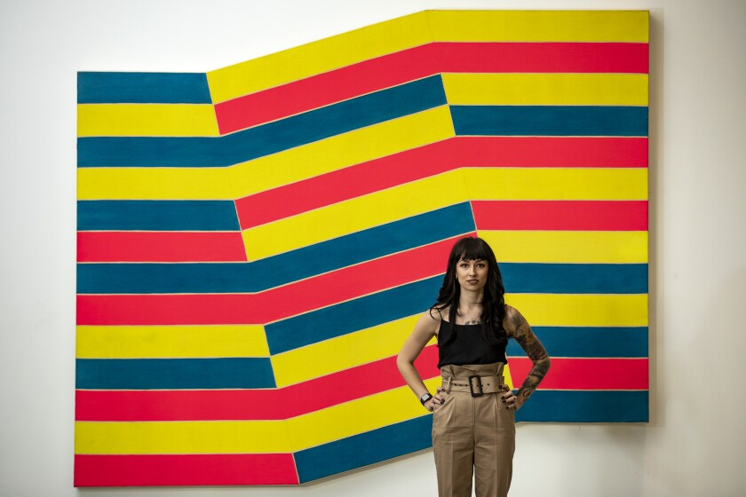 "Kamila Korbela stands in front of ""Bampur"" by Frank Stella."