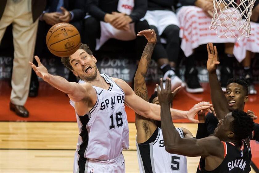 Pau Gasol (i) de Spurs intenta alcanzar el balón durante su partido de baloncesto de la NBA en Toronto (Canadá). EFE