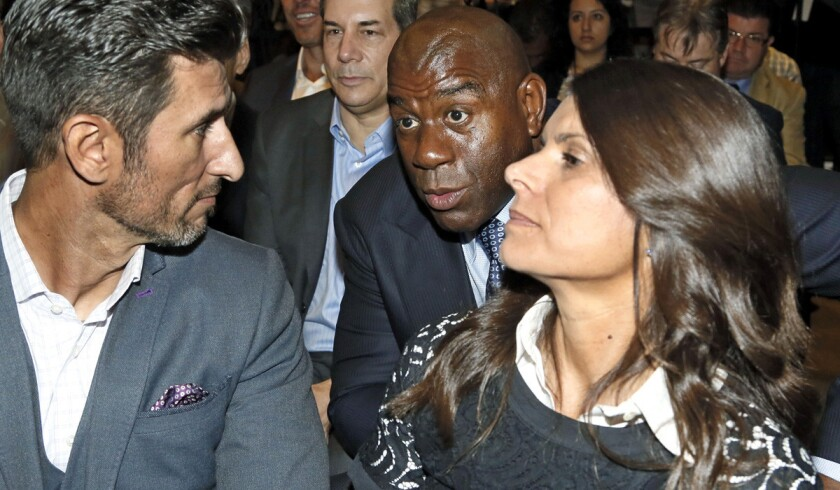 Magic Johnson chats with Nomar Garciaparra, left, and Mia Hamm during a news conference Thursday to announce the launch of a second MLS team in Los Angeles.