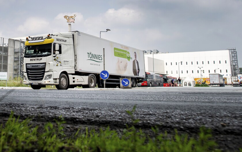 A truck leaves the Toennies meatpacking plant in Rheda-Wiedenbrueck, Germany, Wednesday, June 17, 2020. More than 400 new cases of COVID-19 have been recorded among workers at a large meatpacking plant in western Germany, authorities said Wednesday, in an outbreak that may have been linked to the easing of travel restrictions.( David Inderlied/dpa via AP)