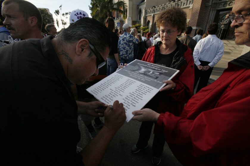 Not seeing the name of a colleague who recently died on the streets, Alfredo Viruegas, left, writes in his name: Mario Sandoval, on a poster carried by Susan Townsend, during a stop for prayer in front of the First Presbyterian Church. At right is Pastor John Townsend.