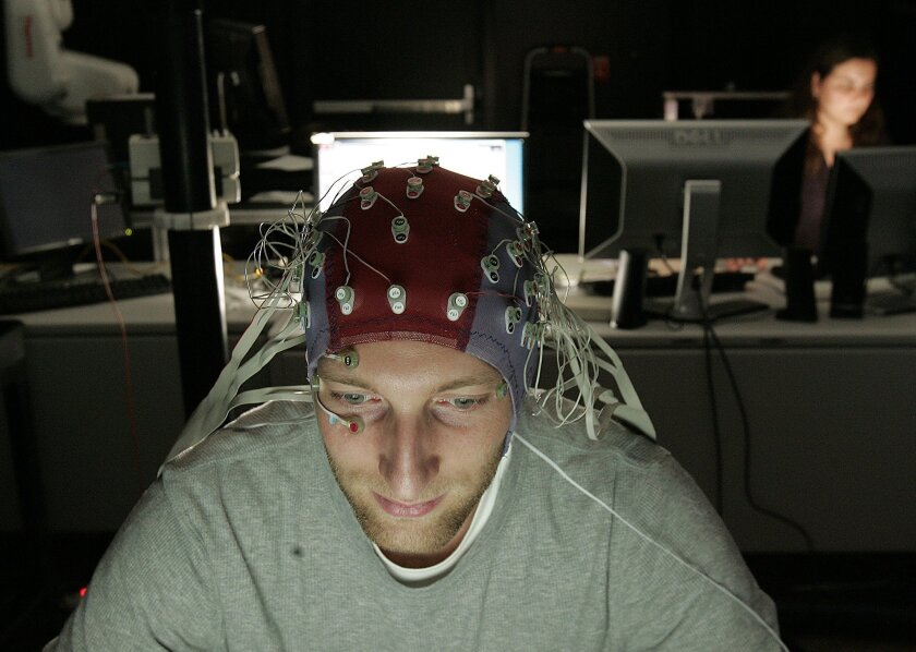 UC San Diego post-doctoral researcher Markus Plank wears an EEG cap while watching video of a human, an android, and a robot. He's collaborating with UCSD neuroscientist Ayse Saygin on a project exploring 'uncanny valley,' the uneasy feeling many people get when they see a robot or animated charact