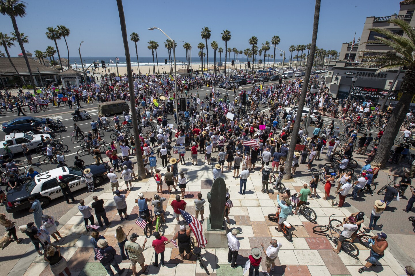 A large crowd gathers during a protest of the governor's stay-at-home orders on Main Street and Pacific Coast Highway in Huntington Beach on Friday, May 1.