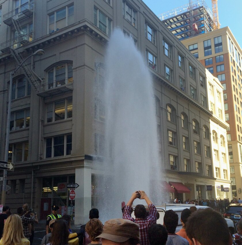 This photo provided by VITAL environments shows a geyser of water shooting four stories high after big-rig struck a fire hydrant at the corner of Bishop and New Montgomery Streets in downtown San Francisco, keeping the city's tech-savvy residents busy posting photos of the drama outside their office windows. KGO-TV reported the roads were reopened around 2:30 p.m., just after the water was shut off. (AP Photo/VITAL environments)
