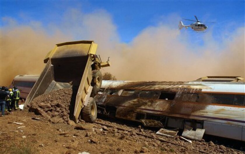 A helicopter flies over the site where a passenger train crashed into a heavy-duty dump truck near Carmonita, southwestern Spain on Monday, Sep. 6, 2010. . (AP Photo/Brigido Fernandez)