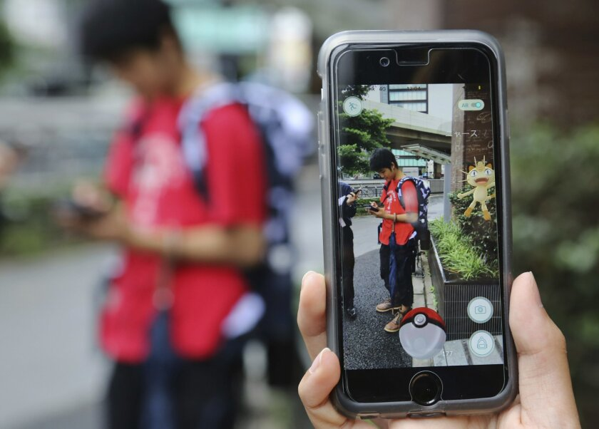 "Japanese students play ""Pokemon Go"" in the street as its released in Tokyo, Friday, July 22, 2016. ""Pokemon Go"" is expected to be a huge hit in Japan, the country of the character's birth. Fans have been eagerly awaiting its release since it first came out more than two weeks ago in Australia, New"