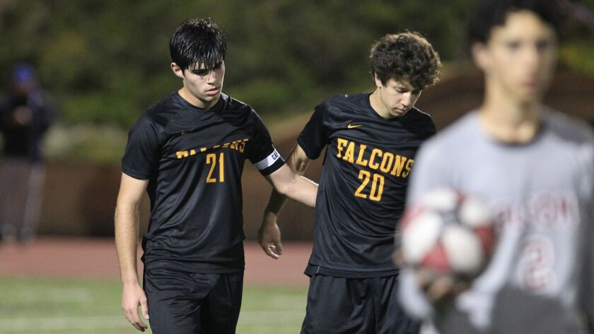 Torrey Pines' Ali Demiralp, left, and teammate Garrett Seamans solemnly walk off the field after los