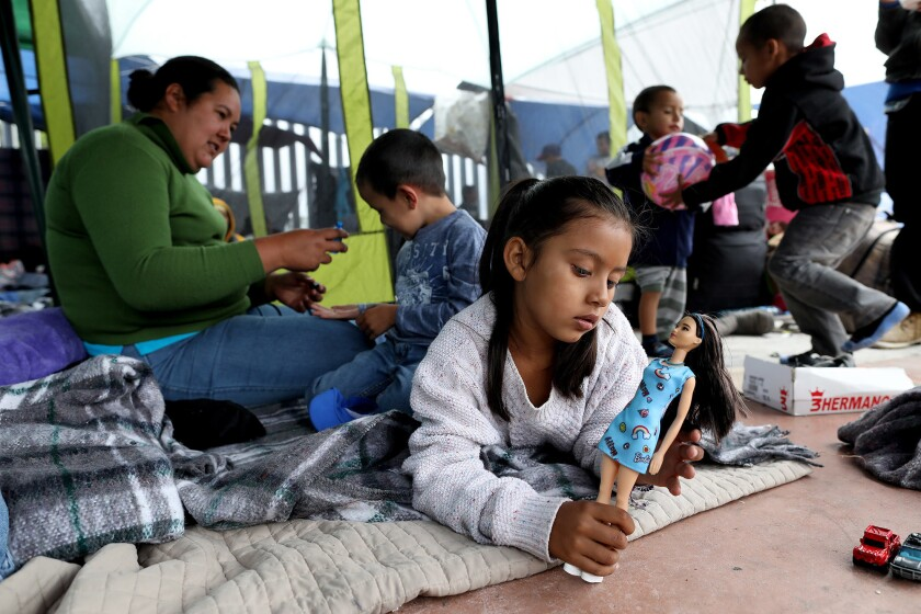 Suany Rodriguez, 6, plays with a doll as her mother and brother sit behind her at a camp in Tijuana. Her mother, Irma Rivera, fled Honduras with the kids after the father was killed and she received a death threat.
