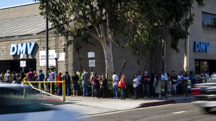Customers wait in a line that stretches around the building and down the block at a California Department of Motor Vehicles Office in South Los Angeles on Aug. 7.