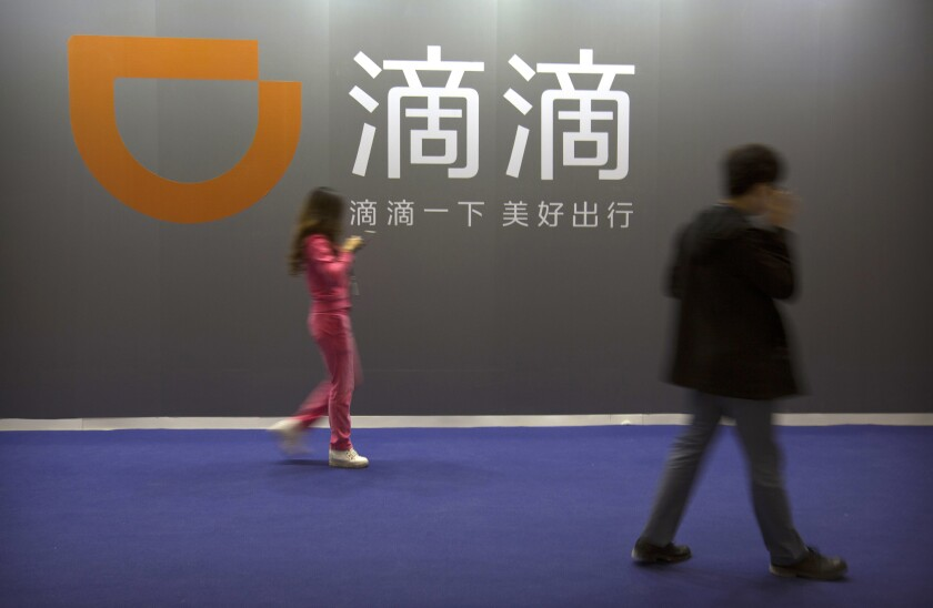 FILE - In this April 27, 2017 file photo, visitors walk past a sign for Chinese ride-hailing service Didi Chuxing at the Global Mobile Internet Conference (GMIC) in Beijing. Chinese regulators have clamped down on the country's largest ride-hailing app, Didi Global Inc., days after its shares began trading in New York. Authorities told Didi to stop new registrations and ordered its app removed from China's app stores pending a cybersecurity review. (AP Photo/Mark Schiefelbein, File)
