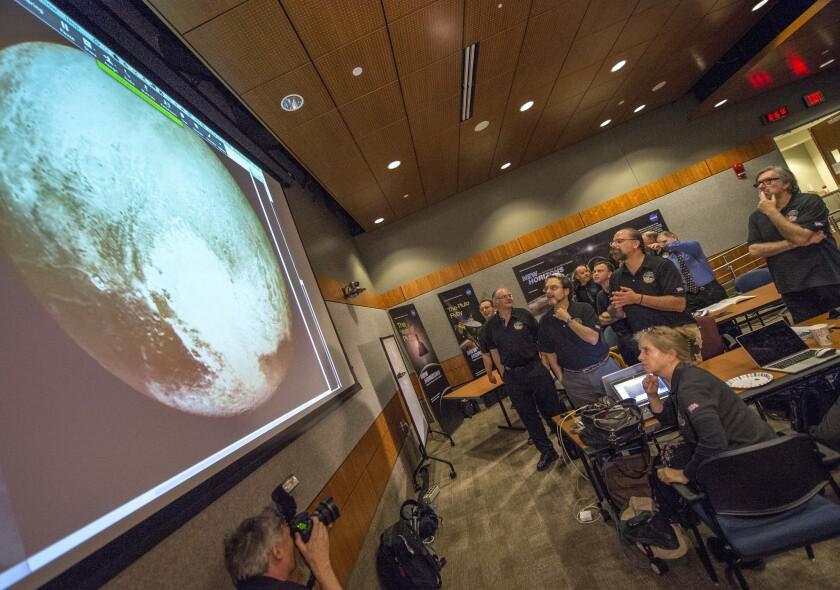 Miembros del equipo científico New Horizons aplauden al ver la imagen más nítida de Plutón antes de su acercamiento máximo el martes 14 de julio de 2015 en el Laboratorio de Física Aplicada de la Universidad Johns Hopkins en Laurel, Maryland.