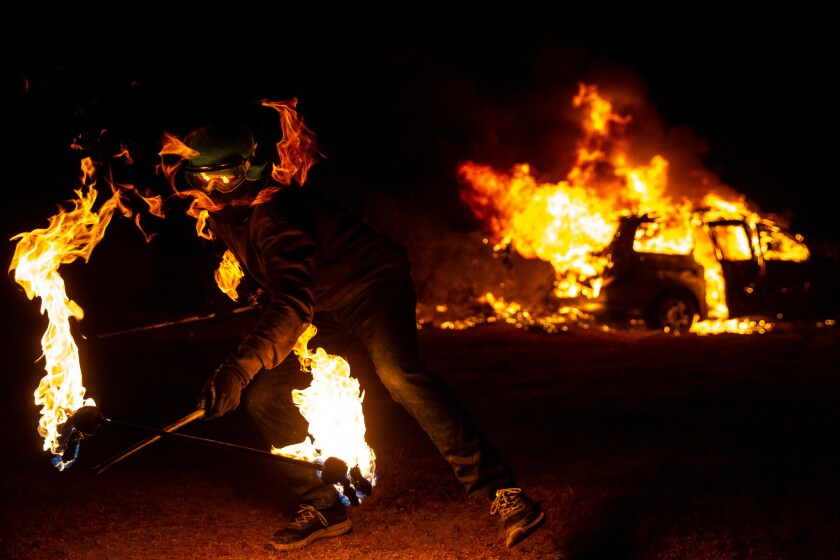 A man twirls a flaming baton as an ailing Honda Odyssey is ritually incinerated at night's end.