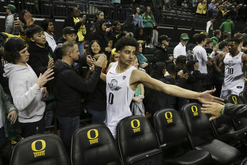Oregon's Will Richardson, center, celebrates with fans after helping his team defeat Colorado 68-60 in an NCAA college basketball game in Eugene, Ore., Thursday, Feb. 13, 2020. (AP Photo/Chris Pietsch)