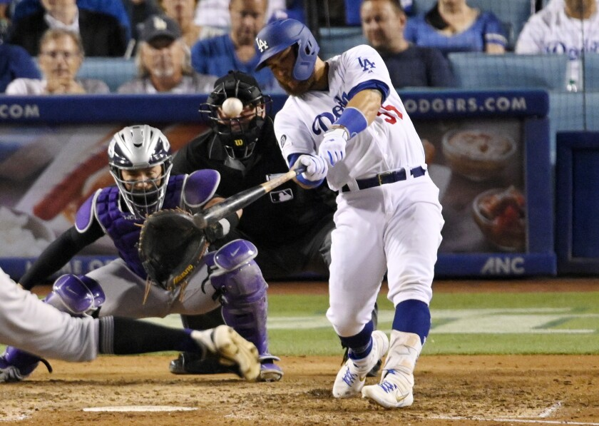 Russell Martin hits a three-run home run in front of Colorado Rockies catcher Tony Wolters during the seventh inning of the Dodgers' 5-3 victory Tuesday.