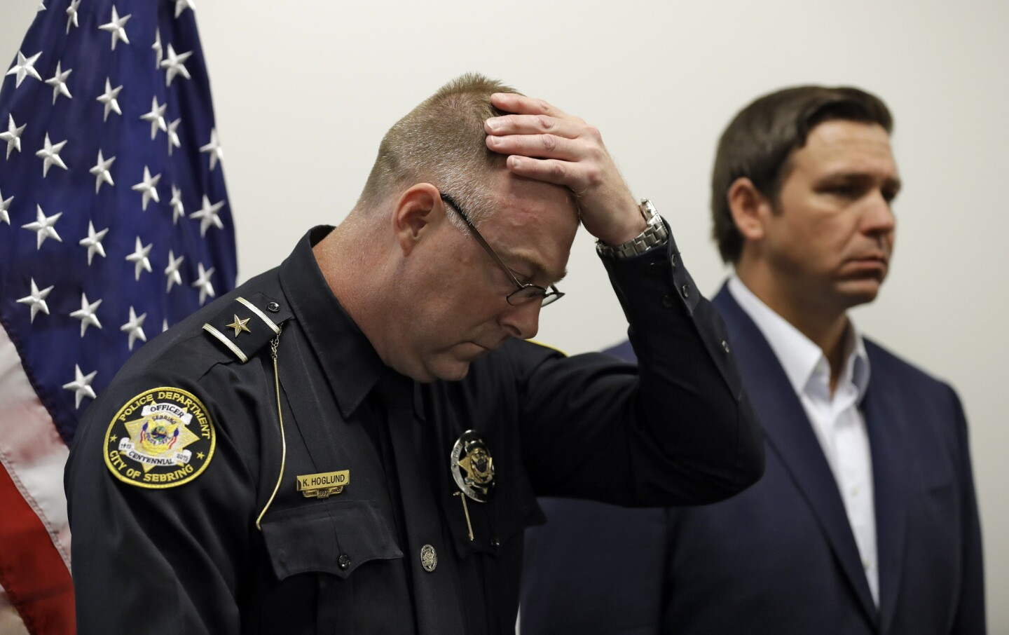 Sebring, Fla., police chief Karl Hoglund wipes his head as he listens to Florida Gov. Ron DeSantis speak during a news conference, on Jan. 23, 2019, in Sebring, Fla., after authorities said five people were shot and killed at a SunTrust bank branch.