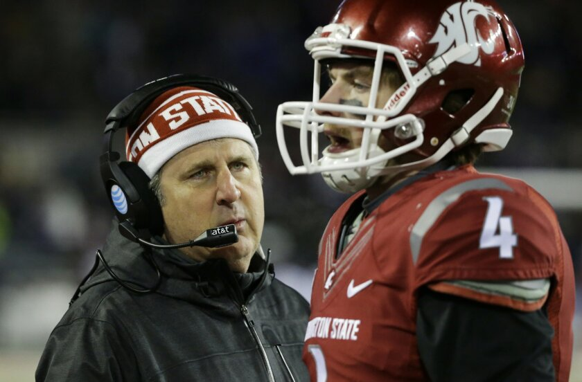 Washington State head coach Mike Leach, left, talks with quarterback Luke Falk, right, on the sideline in the second half of an NCAA college football game against Washington, Saturday, Nov. 29, 2014, in Pullman, Wash. (AP Photo/Ted S. Warren)