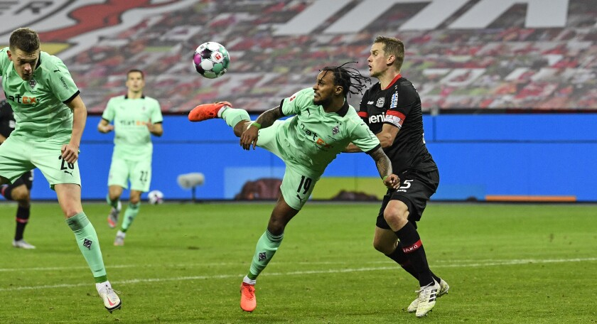 Moenchengladbach's Valentino Lazaro, center, scores an artistic third goal for his side beside Leverkusen's Sven Bender, right, during the German Bundesliga soccer match between Bayer Leverkusen and Borussia Moenchengladbach at the BayArena in Leverkusen, Germany, Saturday, Nov. 8, 2020. (AP Photo/Martin Meissner, Pool)