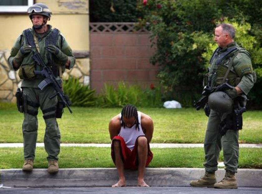 Los Angeles County Sheriff's Deptartment personnel watch over a man detained during a gang sweep conducted to crack down on a violent clique of the Bloods gang, centered in the Compton area.