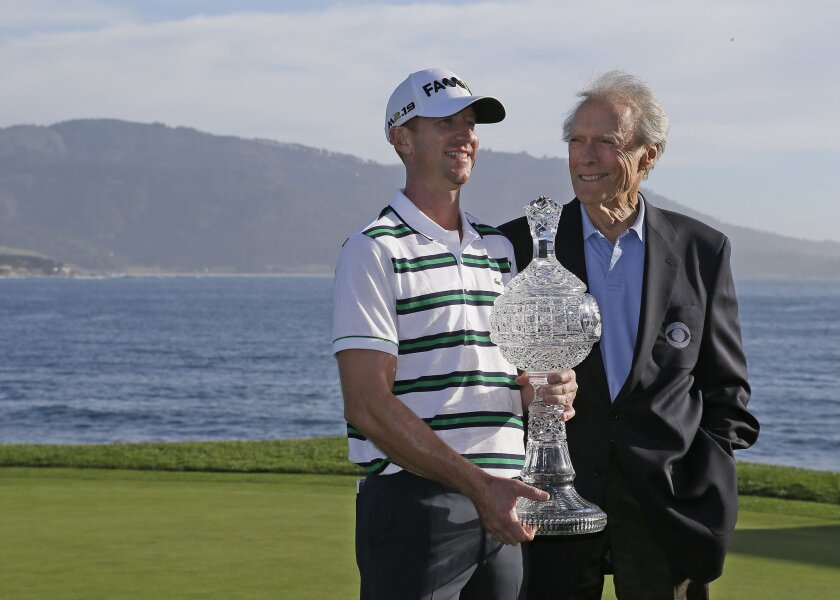 Vaughn Taylor, left, poses with his trophy and Clint Eastwood, right, on the 18th green of the Pebble Beach Golf Links after winning the AT&T Pebble Beach National Pro-Am golf tournament Sunday, Feb. 14, 2016, in Pebble Beach, Calif. Taylor won the tournament by one stroke over Phil Mickelson. (AP