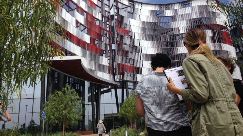 A silver and red screen symbolizing a genome was nominated for an Orchid. Jurors visit the building