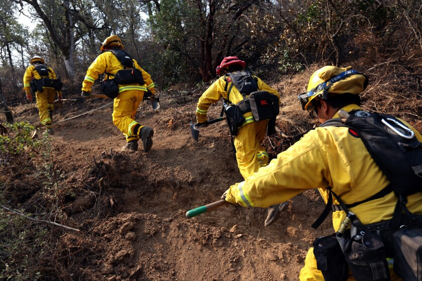 Firefighters make their way up a hillside along Water Trough Road in Lake County, south of Clearlake, on Aug. 5, 2015.