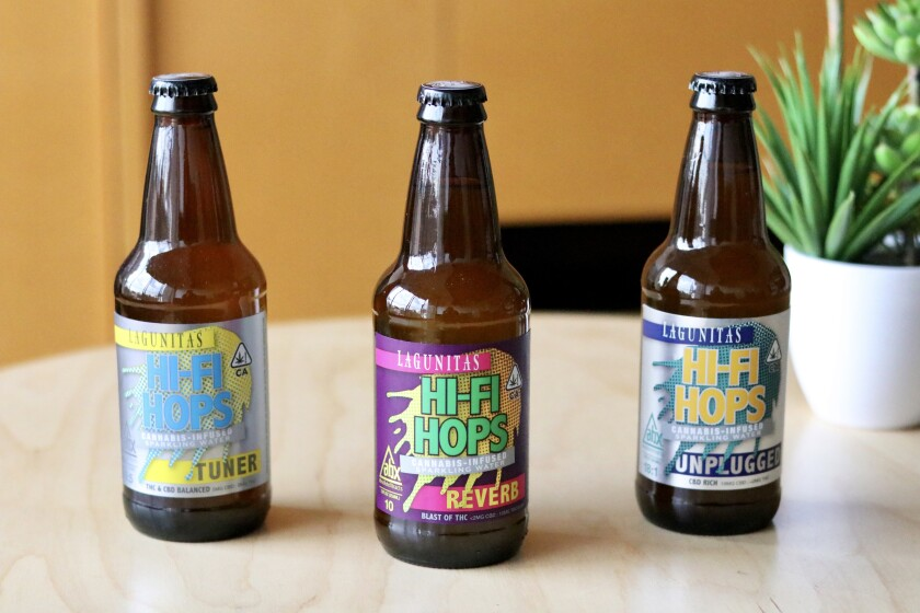 Three bottles with colorful labels sitting on a table.