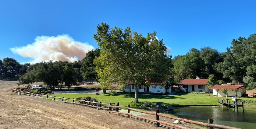 A smoke column from the Alisal fire builds in the distance behind former President Ronald Reagan's Rancho del Cielo