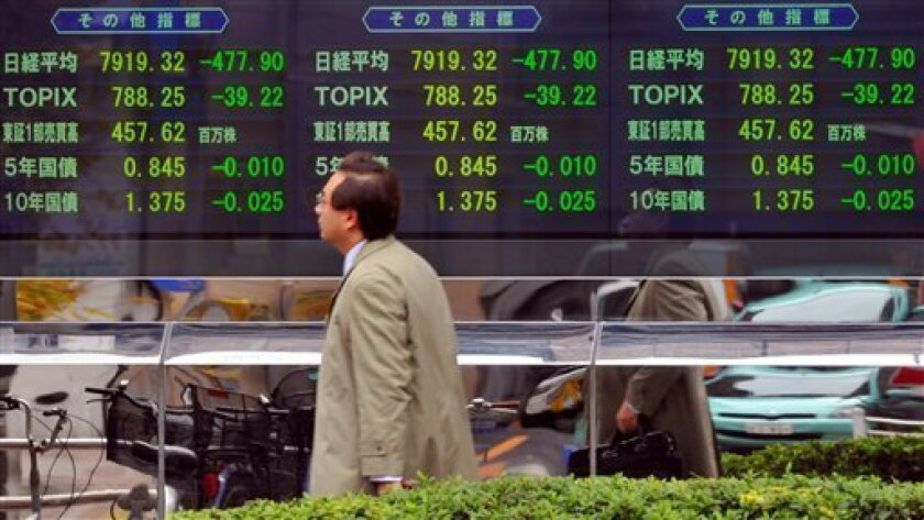 A Japanese man makes his way past an electric market board in central Tokyo, Tuesday, Dec. 2, 2008. Japan's Nikkei stock index tumbled more than 5 percent in early trade Tuesday following massive losses on Wall Street amid growing gloom over the global economy. (AP Photo/Katsumi Kasahara)