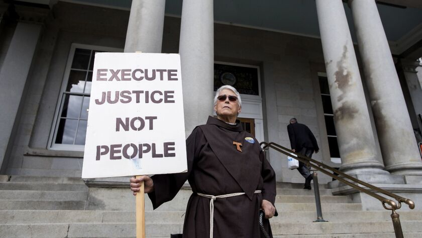 The Rev. Cynthia Morse from the Order of Ecumenical Franciscans greets lawmakers as they enter the S