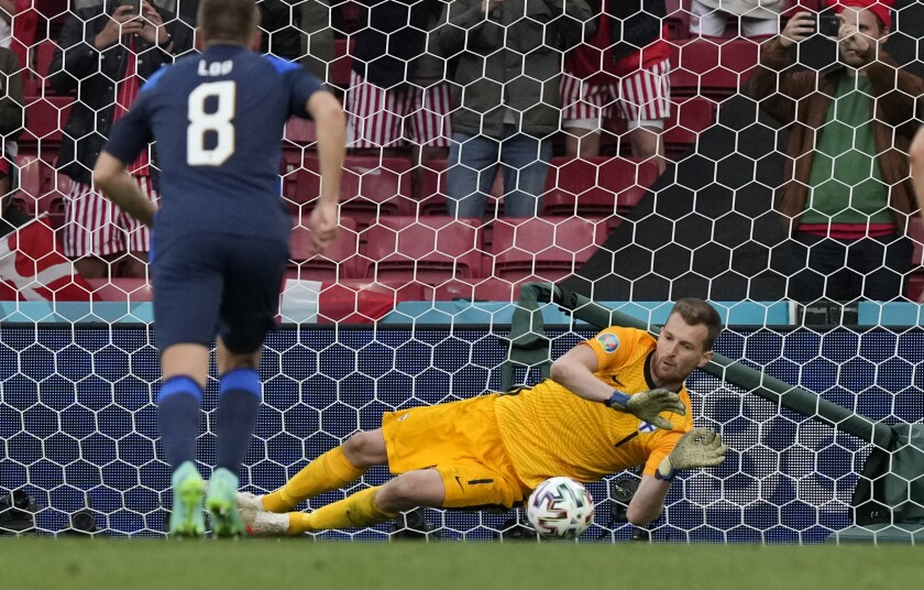 Finland's goalkeeper Lukas Hradecky makes a save during the Euro 2020 soccer championship group B match between Denmark and Finland at Parken stadium in Copenhagen, Saturday, June 12, 2021. (AP Photo/Martin Meissner, Pool)