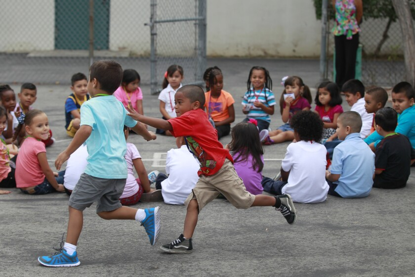 Expanded Transitional Kindergarten (ETK) pre-kindergarten students Jakobe Mara, right, chases Tyler Rahman as they play a duck-duck-goose game during their first day of school at 186th Street Elementary in Gardena, on Aug. 18.