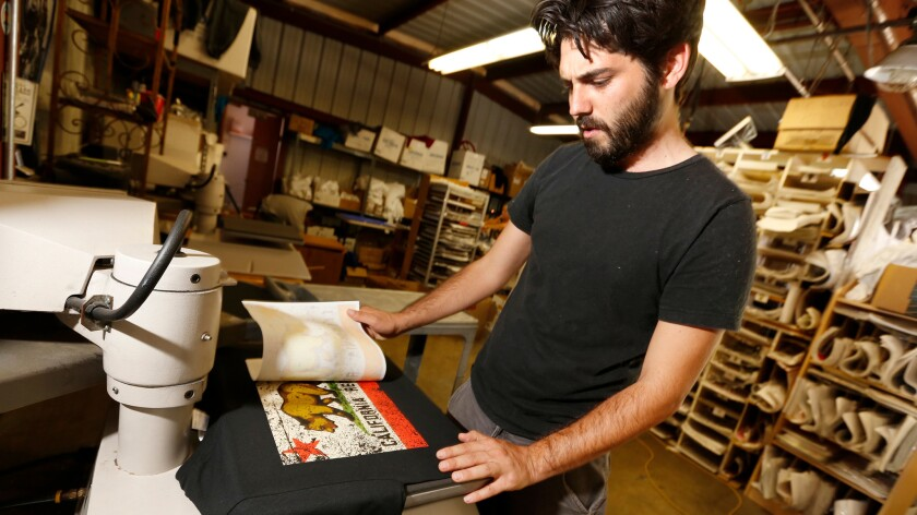 Willie Travis makes T-shirts at The Dolphin Shirt Company.
