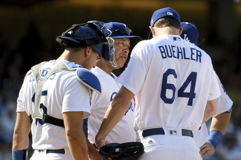 Dave Roberts talks with pitcher Walker Buehler during a bases-loaded jam near the end of last season.
