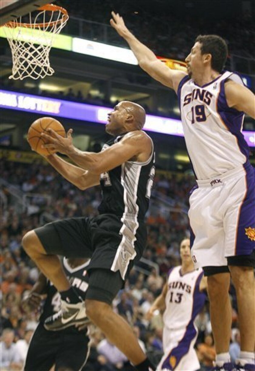 San Antonio Spurs forward Richard Jefferson slips in for a basket past Phoenix Suns forward Hedo Turkoglu during the first half of an NBA basketball game, Wednesday, Nov. 3, 2010, in Phoenix. (AP Photo/Ralph Freso)