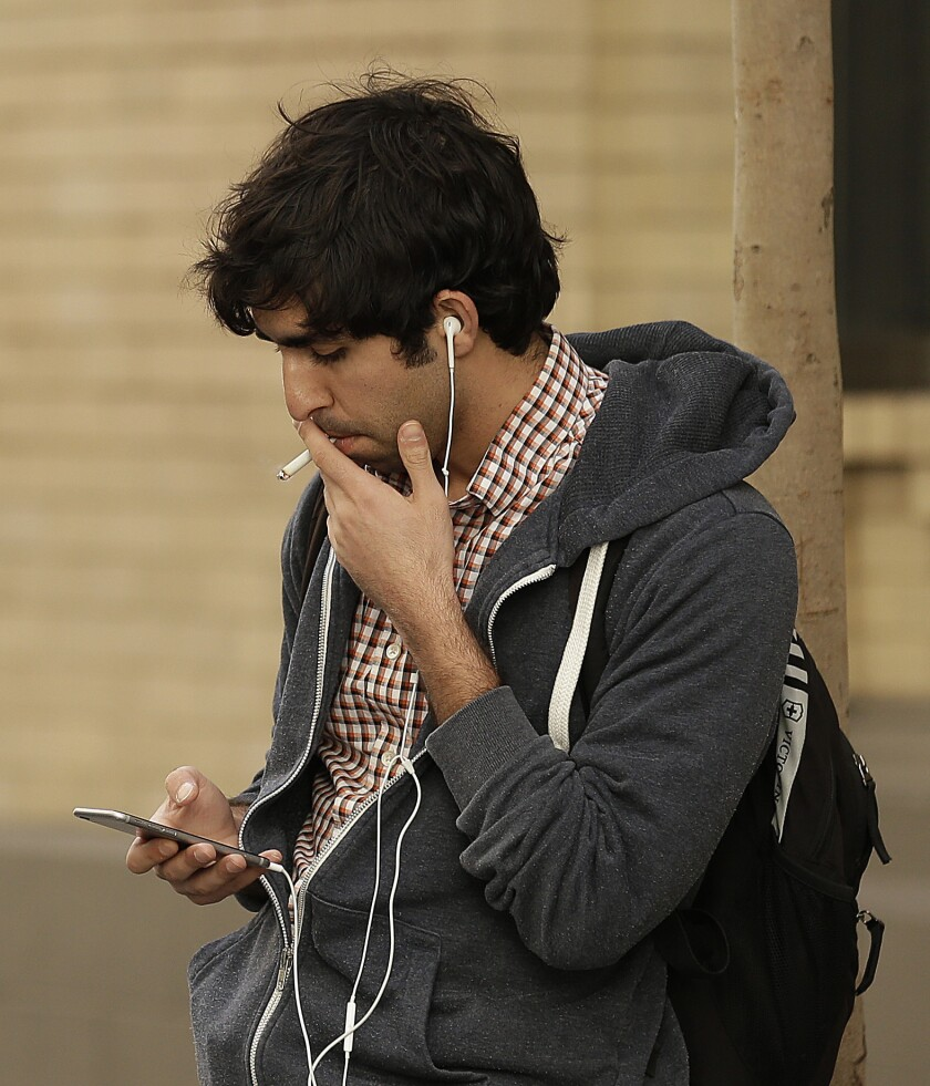 A man smokes a cigarette this week in San Francisco. The state Assembly on Thursday voted to increase the minimum age to buy tobacco from 18 to 21 and to regulate electronic cigarettes.
