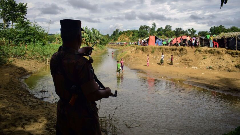 A Bangladeshi border guard orders Rohingya refugees to return to the Myanmar side of a small canal b
