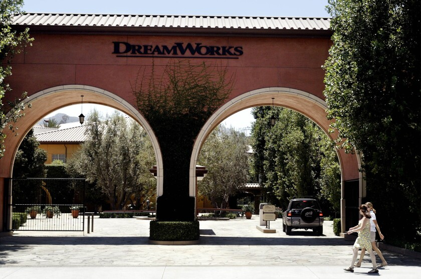 People walk past the entrance to DreamWorks Animation's studio in Glendale, Calif. DreamWorks has signed a deal to sell and lease back the studio property.