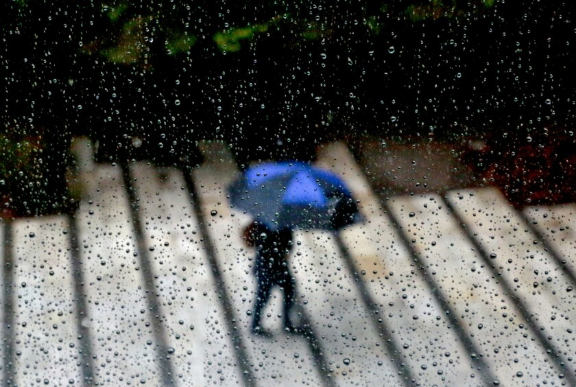 A pedestrian with an umbrella walks in Sacramento during a rainstorm in April. El Niño conditions are strengthening in the Pacific Ocean, forecasters said.