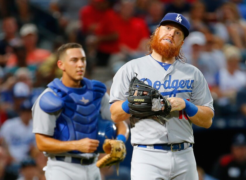 Dodgers third baseman Justin Turner reacts after colliding with catcher Austin Barnes while trying to catch a pop fly.