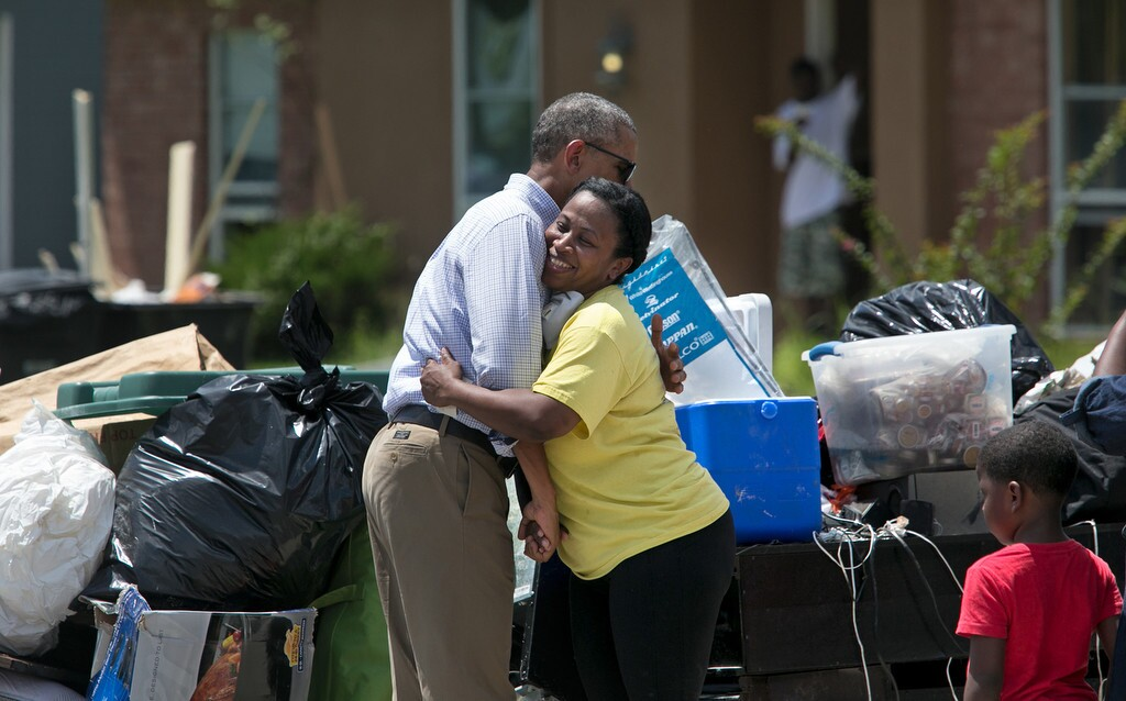 President Barack Obama hugs Marlene Sanders as he visits with with residents of Castle Place, a flood-damaged area of Baton Rouge, La., Tuesday, Aug. 23.