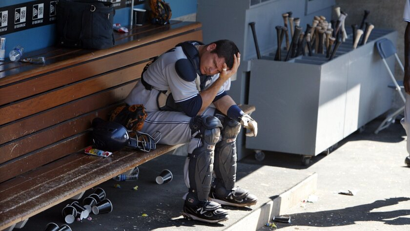 Padres catcher Rob Johnson hangs his head in the dugout after a loss against the L.A. Dodgers on July 9.