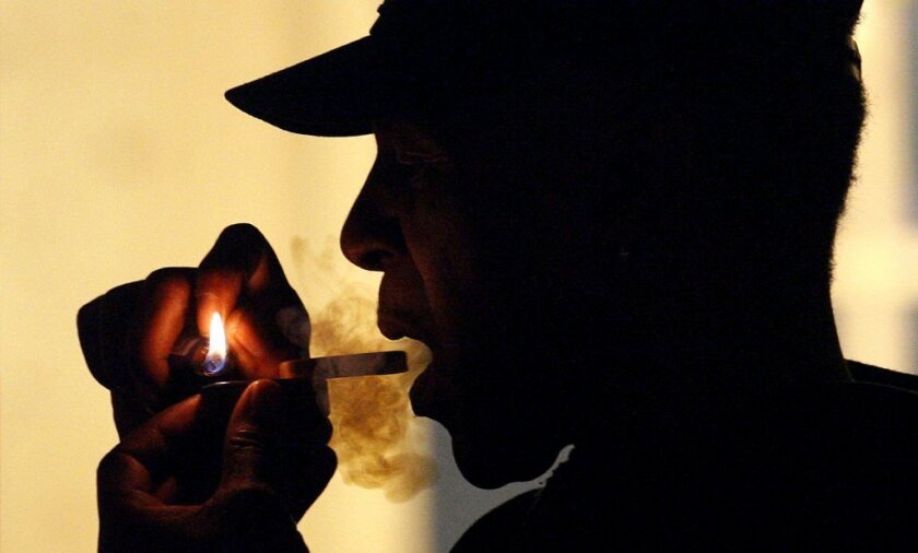 An unidentified man smokes medical marijuana during karaoke night at the Cannabis Cafe, in Portland, Ore. Delaware became the latest state to decriminalize the drug on Thursday, and several other legislative items and ballot measures could push more states closer to legalization by the end of the year.