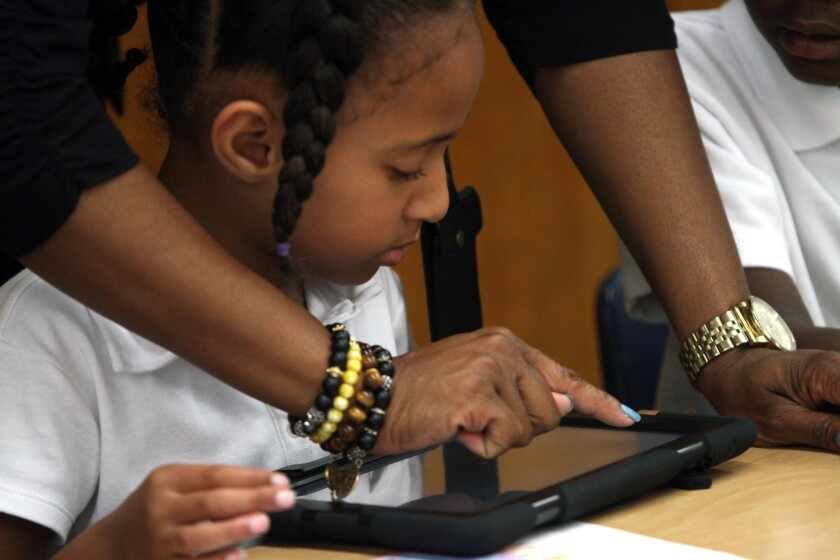 Student gets help as she and her teacher explore the possibilities with their new LAUSD-provided iPads.